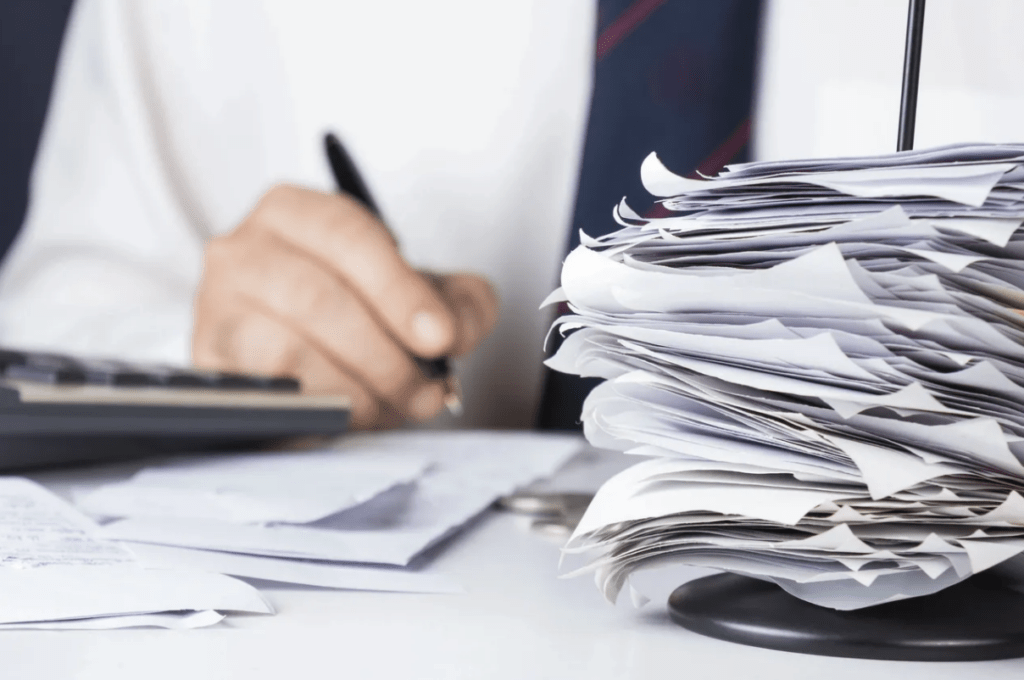 stock photo of paperwork and person holding pen